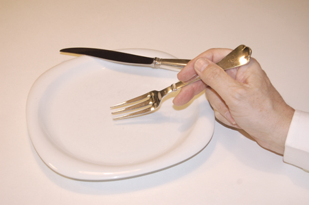 eating with a fork while the knife is resting on the plate